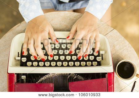 Girl Typing On The Old Typewriter With A Cup Of Coffee Outdoors