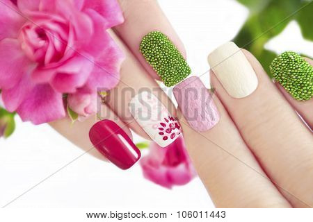 Multicolored manicure with flower.