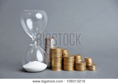 Hourglass with coins on gray background
