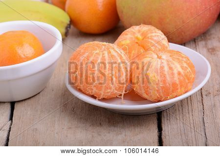 Bowls Of Slices Mandarin With Apple On Rustic Wooden Background
