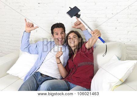 Attractive Couple Taking Selfie Photo Or Shooting Self Video With Mobile Phone And Stick Sitting At