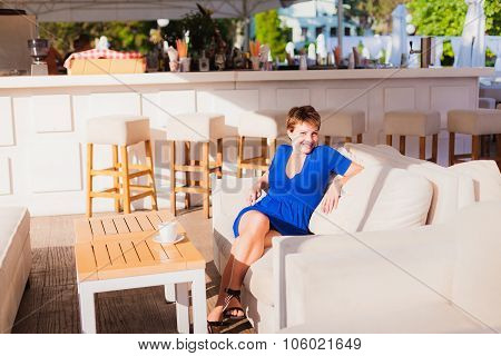 Happy young woman  sitting on sofa in bar