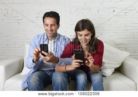 Young Attractive Couple Of Man And Woman Together At Home Couch With Arms Interlaced Using Mobile Ph