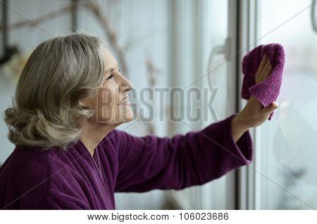 Senior woman cleaning window