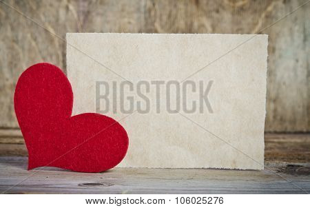 The Form For A Card On Wooden Background .   Handmade Heart From Red Felt Is  In The Left Corner Of