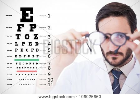 Doctor wearing lab coat looking through eyeglasses against eye test