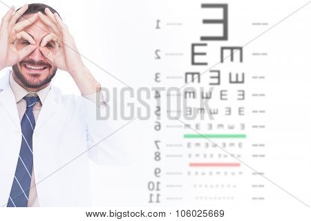 Smiling doctor forming eyeglasses with his hands against eye test