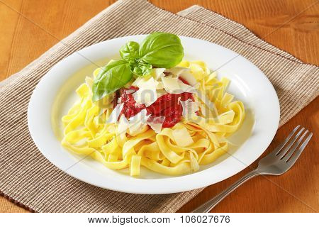 plate of fettuccine pasta and tomato sauce on brown place mat