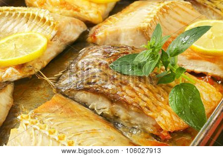 close up of roasted carp fillets in baking tin
