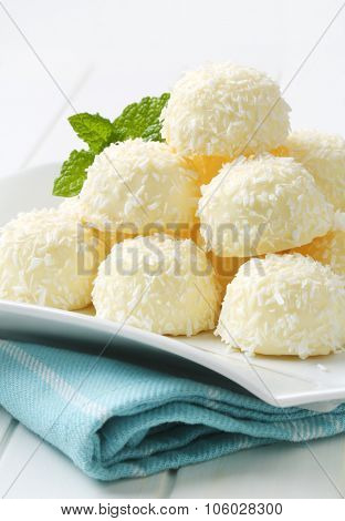 stack of white coconut truffles on white square plate and blue dishtowel