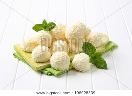 white coconut truffles on green wooden cutting board and place mat