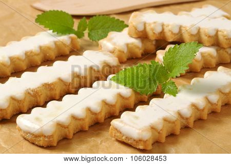 close up of fluted cookies with lemon glazing on baking paper