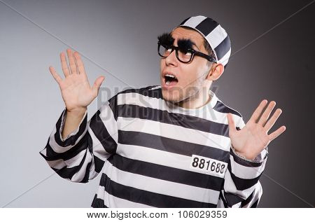 Funny prisoner with faked eyebrows in striped uniform