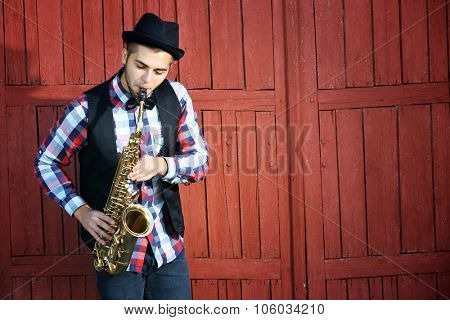 Handsome happy man in hat plays music on sax in front of red wooden background