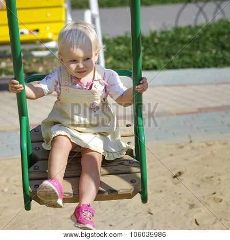 Litlle girl on a swing at the kids playground