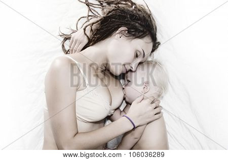 Mother feed little baby by breast in the bed.