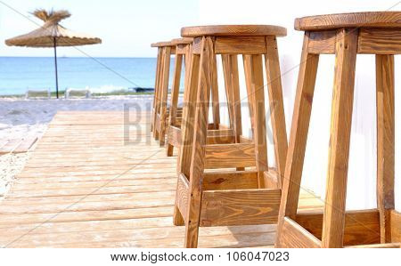 Beach bar wooden stools in a row, close up