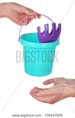 Concept of childish goods sale -one woman hand gives toys to another, isolated on white background