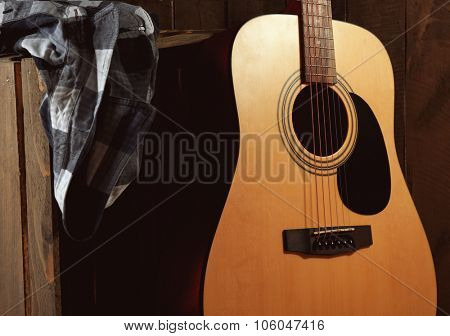 Guitar and shirt left on crate on wooden wall background