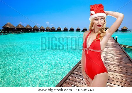 The girl in a bathing suit and a cap of Santa Claus and ocean on a background. Maldives.