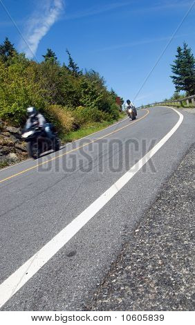 Two Motorcyclists Coming Down A Mountain Road