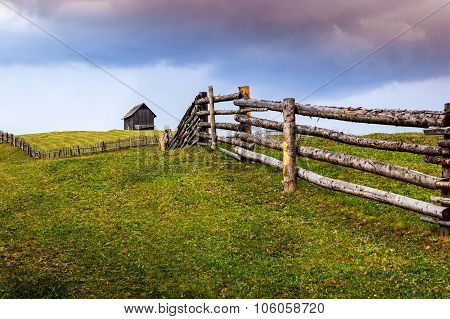 Field Of Green With Wooden House On The Hill