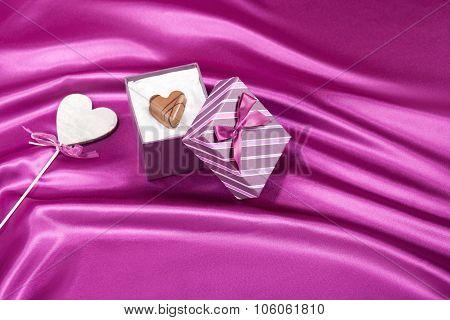 Valentine symbol in gift box on pink