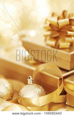 Golden christmas gift box and christmas balls on bokeh light background