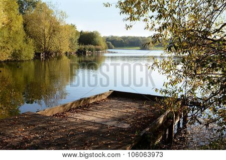 Wooden Jetty In Fall Looks Out Over A Lake