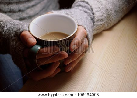 Woman Holds Hot Drink At A Table Under Lamplight