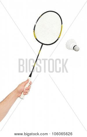 Hand with badminton racket and shuttlecock isolated on white background