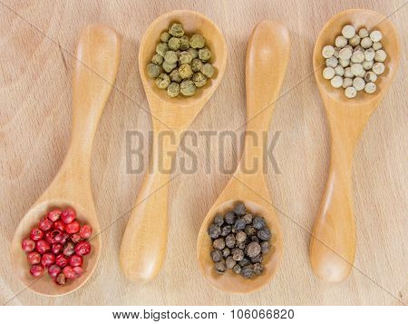 wooden teaspoons with fresh assorted spices on wooden table