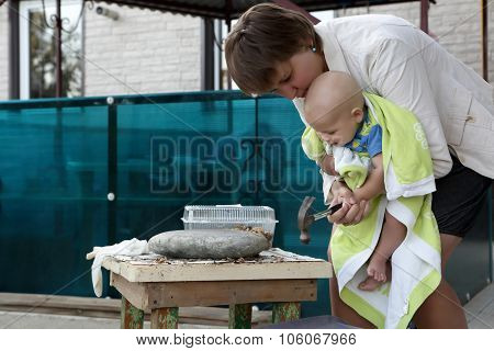 Mother With Baby Cracking Nuts