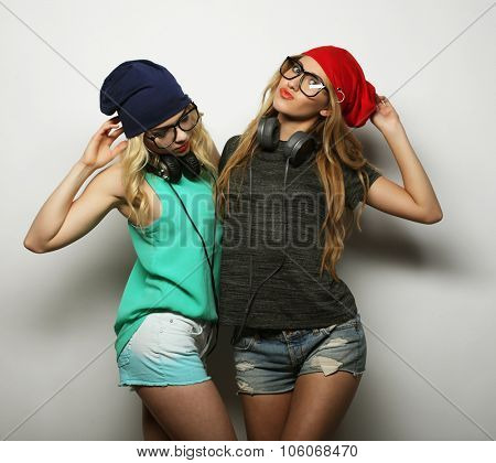 Studio lifestyle portrait of two best friends hipster girls wearing stylish bright outfits, hats, denim shorts and glasses, going crazy and having great time together. Young and beauty.