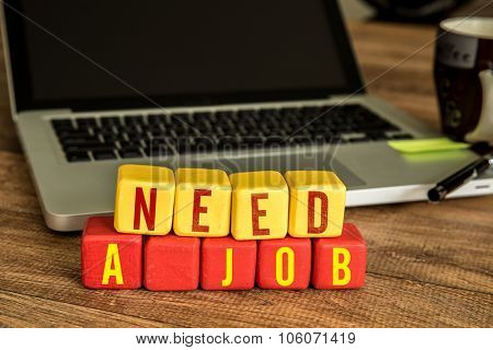 Need a Job written on a wooden cube in front of a laptop