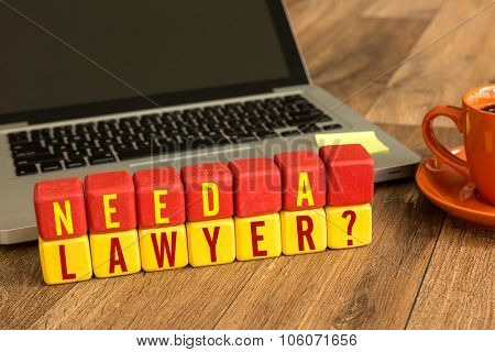 Need a Lawyer? written on a wooden cube in front of a laptop