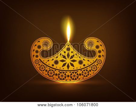 Floral design decorated golden illuminated lit lamp on glossy brown background for Indian Festival of Lights, Happy Diwali celebration.