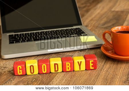 Goodbye written on a wooden cube in front of a laptop