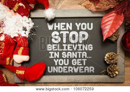 Blackboard with the text: When You Stop Believing In Santa... You Get Underwear in a christmas conceptual image