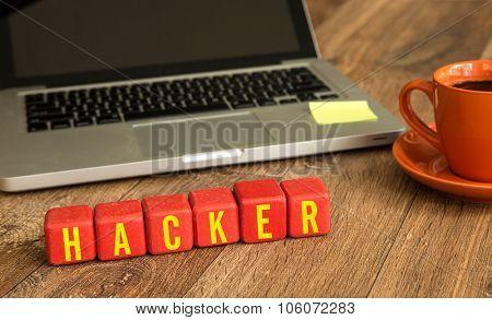 Hacker written on a wooden cube in front of a laptop