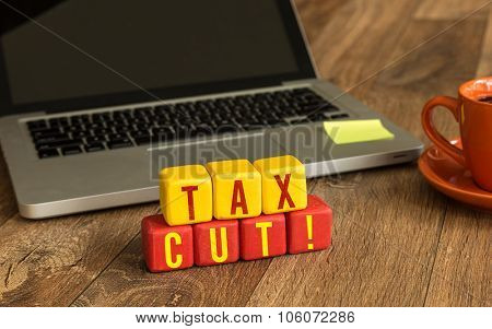 Tax Cut written on a wooden cube in front of a laptop