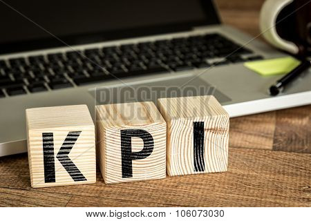 KPI (Key Performance Indicator) written on a wooden cube in front of a laptop