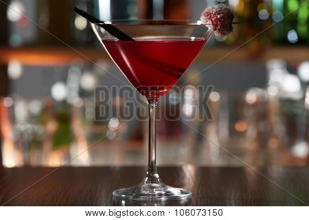 Red alcohol cocktail with sugared cherry on the bar counter, close up