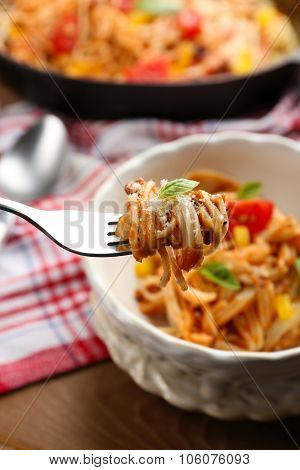 Homemade Spaghetti Bolognese with parmesan cheese in white bowl, on color wooden background
