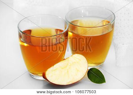 Glasses of apple juice on windowsill
