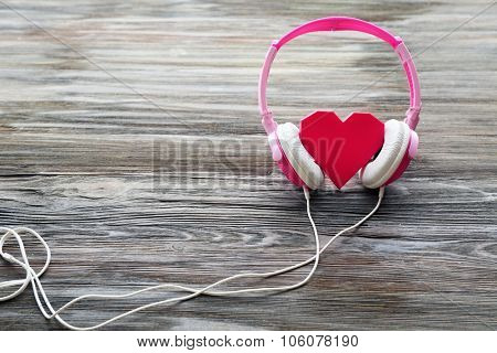 Pink headphones with rosy heart on wooden background