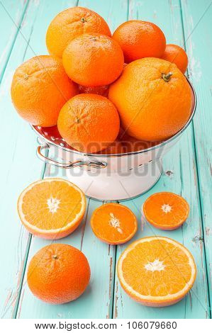 Oranges and Tangerines in retro colander on the old wooden table.