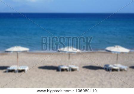 Greece. Kos. Kefalos Beach. Chairs And Umbrellas On The Beach. In Blur Style