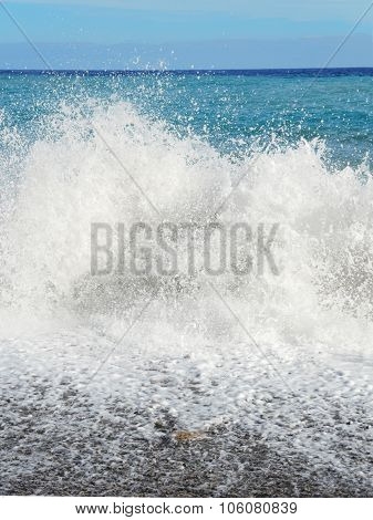 Big wave with sea foam and blue water.
