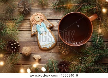 gingerbread handmade angel on the wooden background with fir branches